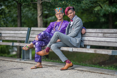 A couple of black grooms from the Caribbean sitting on a park bench at Granite Prospect - Brooklyn Bridge Park cross-legged, one wearing open toe sandals; the other stylish red wine socks with grey and black patterns; both are smiling and looking into the camera as if they were interrupted mid-conversation to take the picture; pic taken post ceremony officiated by queer officiant at Once Upon A Vow.