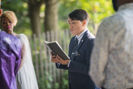 LGBTQ officiant from Once Upon a Vow, a masculine presenting woman with short, partially shaved haircut in a blue suit with notable accessories is reading the ceremony from her black ceremonial book with attentive guests in the background.