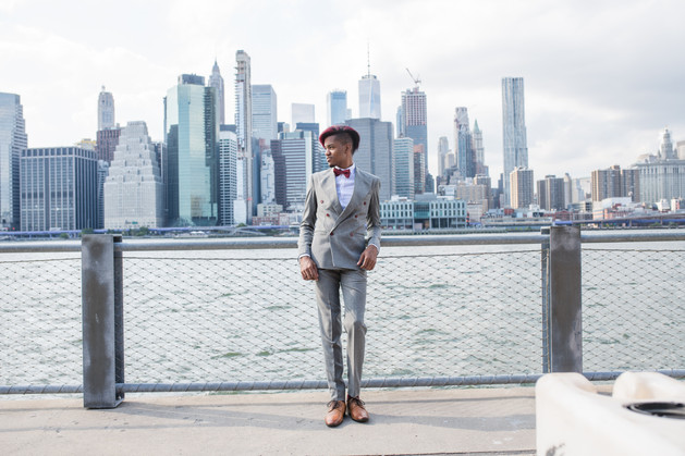 Groom wearing charcoal grey suit with red wine bow tie and red wine hair looking to his right with the NYC skyline leaning against water barrier with NYC skyline behind him; pic taken post ceremony officiated by queer officiant at Once Upon A Vow.