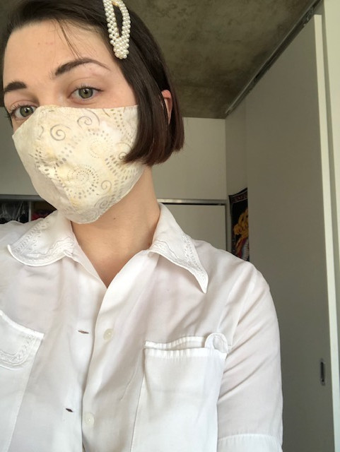 Megan, a white woman with cropped brown hair is staring at the camera. She is wearing a white and beige cloth face mask, a collared white shirt, and a large pearl hair clip.