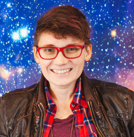 Image caption: Kate is smiling into the camera. She is wearing bright red glasses and is posed in front of a background picture of a galaxy.