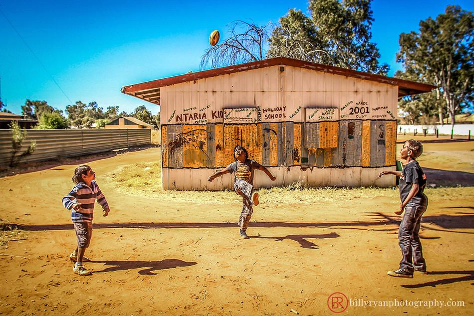 Aboriginal children kicking a ball