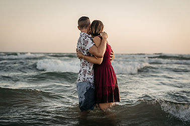 Couple standing in the ocean hugging each other at sunset