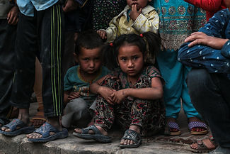 Portrait of two nepalese children sitting a crowd for the photography services page