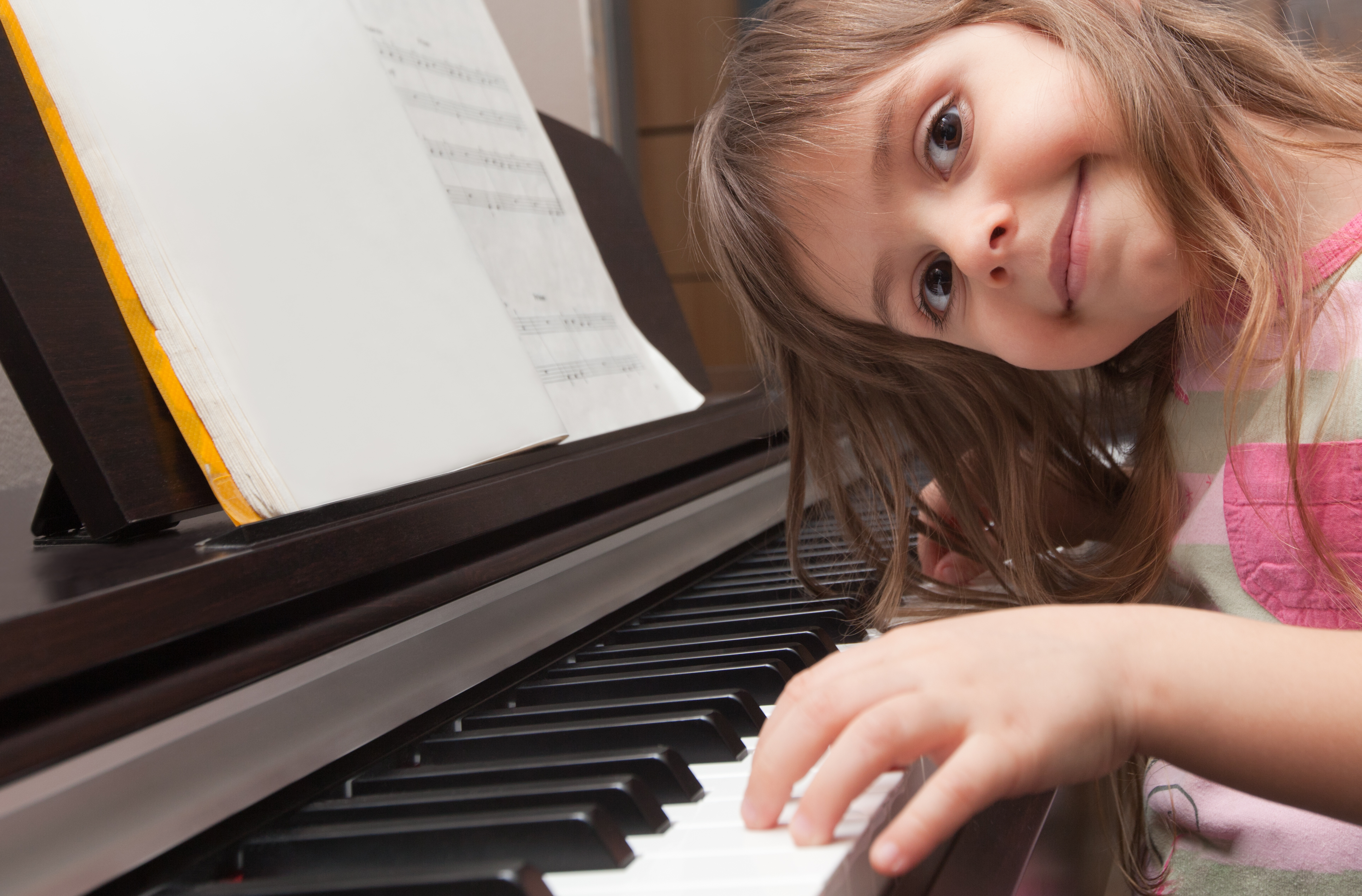 Little girl smiling at piano keyboard