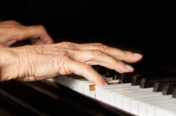 Old person's hands playing the piano.jpg Close up view of skin texture and piano keys