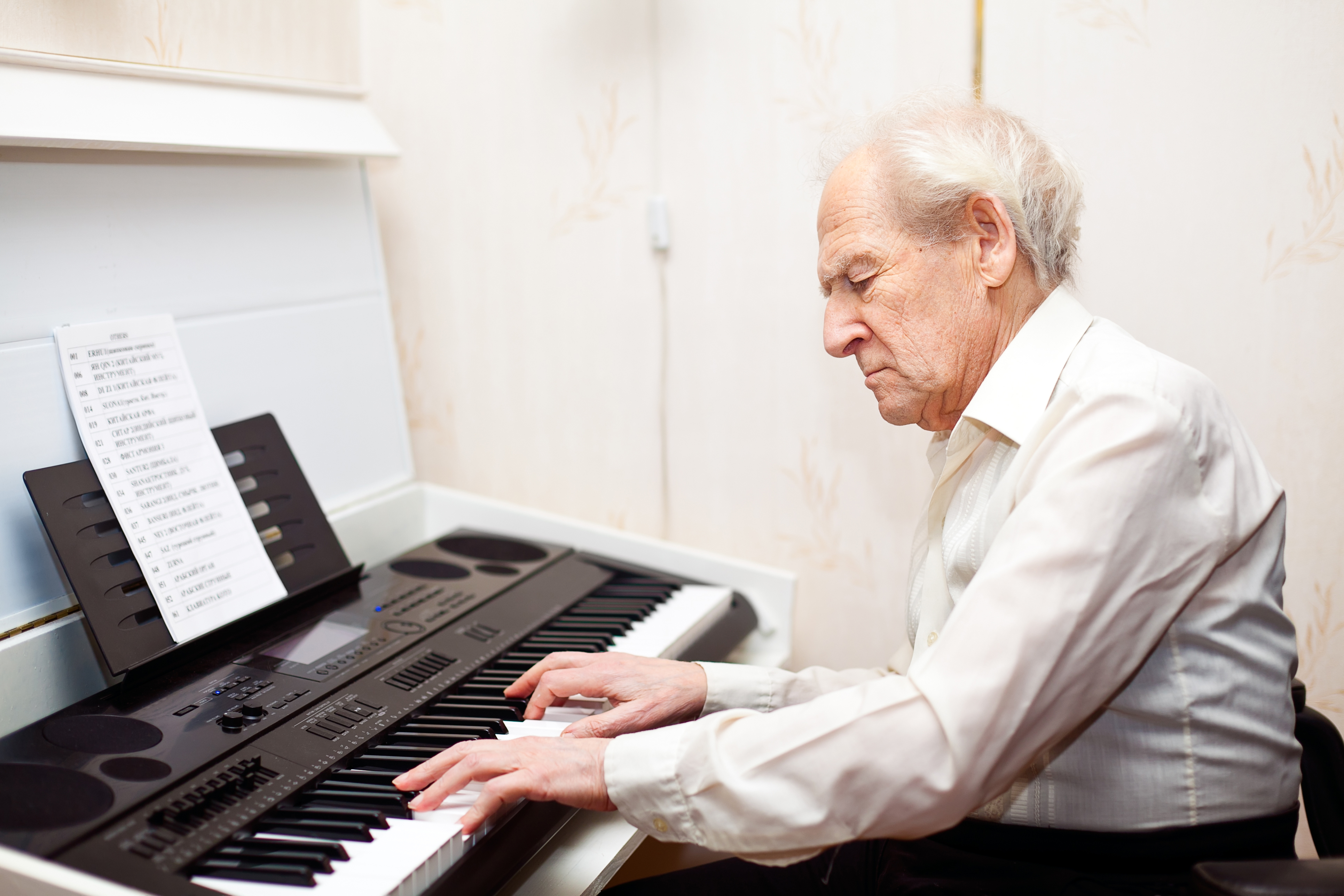 grey-haired senior man playing piano