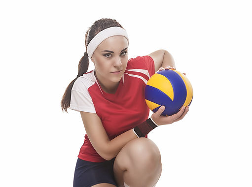 Female volleyball player kneeling in red and white jersey white white headband holding yellow and blue volleyball