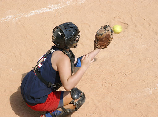 Youth softball player in full uniform and padding catching a fast softball pitch