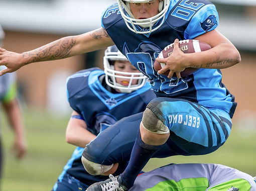 Football player holding the football avoids tackle by opposing team member
