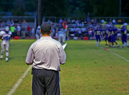 Male football coach looking out over football field while teams huddle before the next play