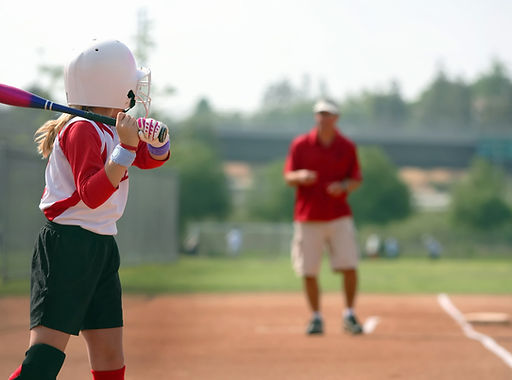 Softball coach in the background instructing youth softball player at bat in the foreground