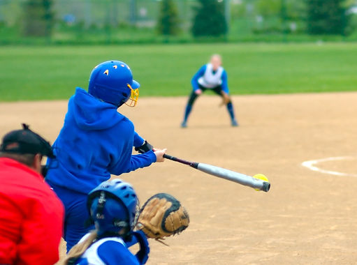 Softball player in blue swinging at a pitched softball with another player ready to catch in the background