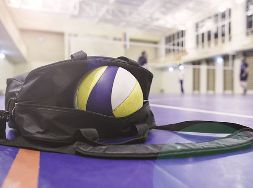 Bag with volleyball exposed on gym floor with volleyball net and players in the background