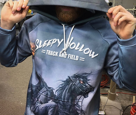 Man wearing great and blue hoodie with Sleepy Hollow Track and Field text and headless horseman design printed on it