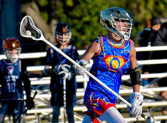 Female lacrosse in blue, yellow, and red uniform running with lacrosse ball in lacrosse stick