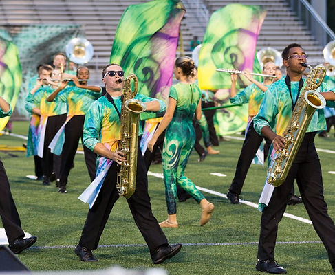 Marching band and color guard members in yellow, green, and pink uniforms performing on field