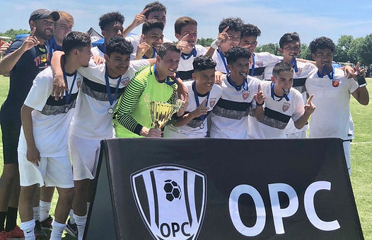 Male soccer team in white uniforms showing off medals and trophy after winning