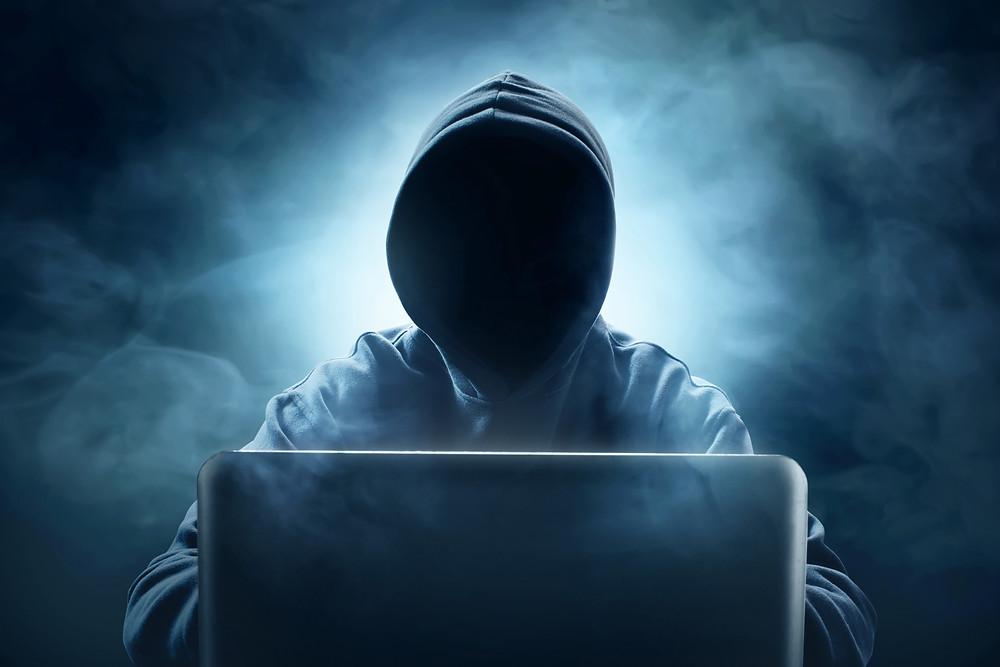 Man wearing hoodie at laptop.