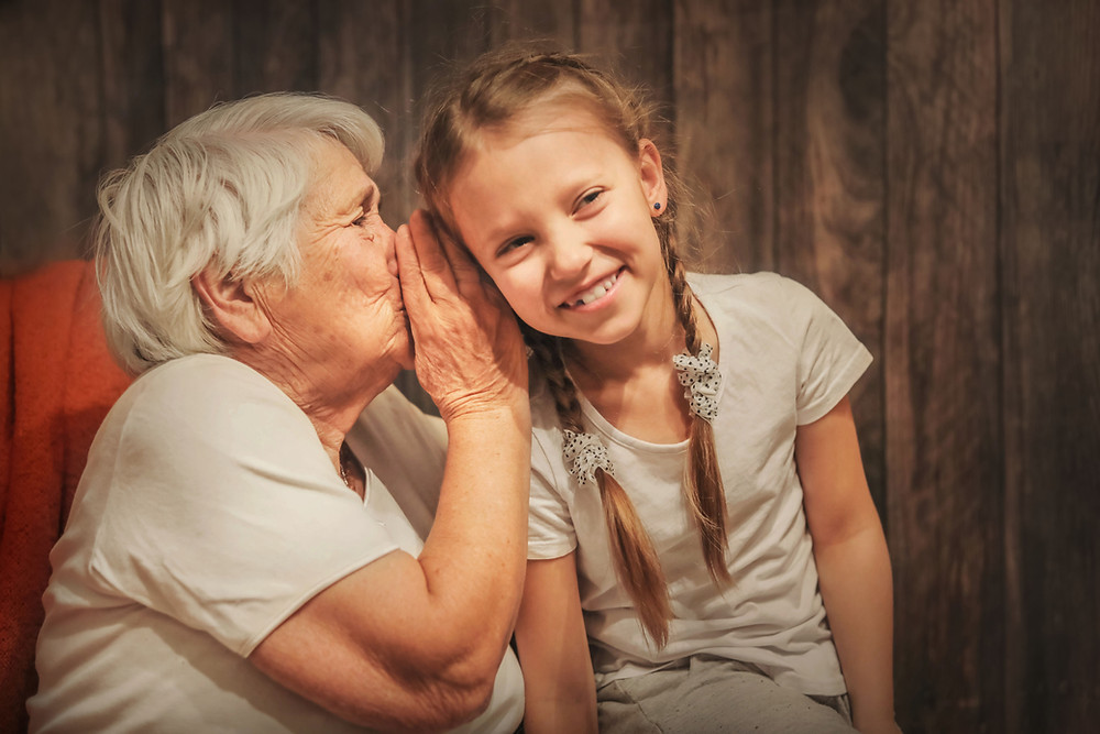Grandmother whispers to young girl.