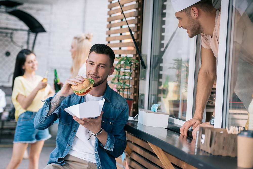 Man eating burger from shop.