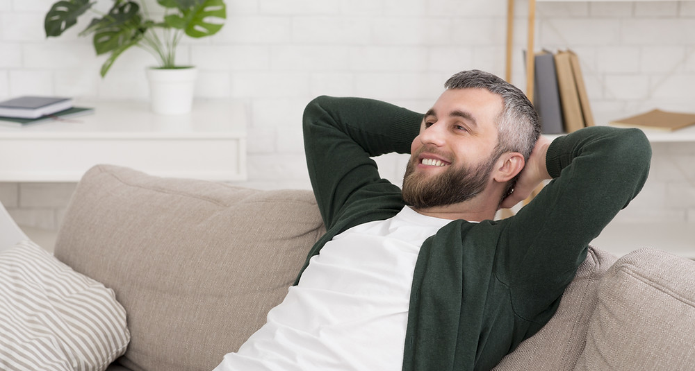 Man lays on sofa with hands behind back.