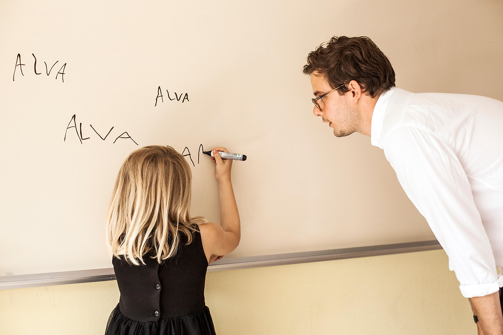 Young girl learning to write her name.