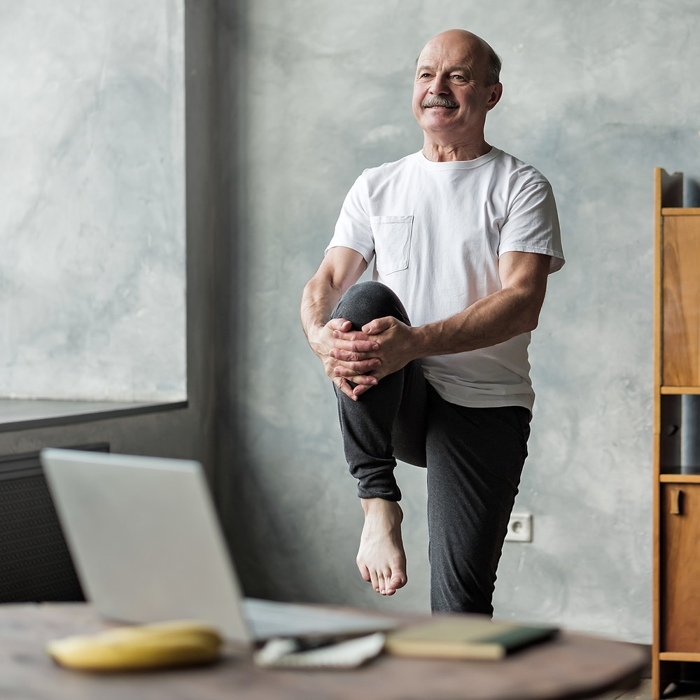 Man stretching in front of laptop.