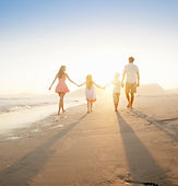 Family of four running into the sunset on the beach