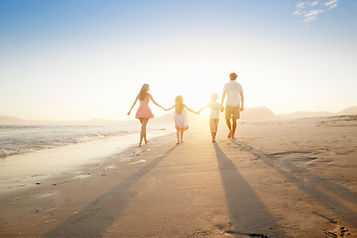 Family of four walking on a beach into a sunset