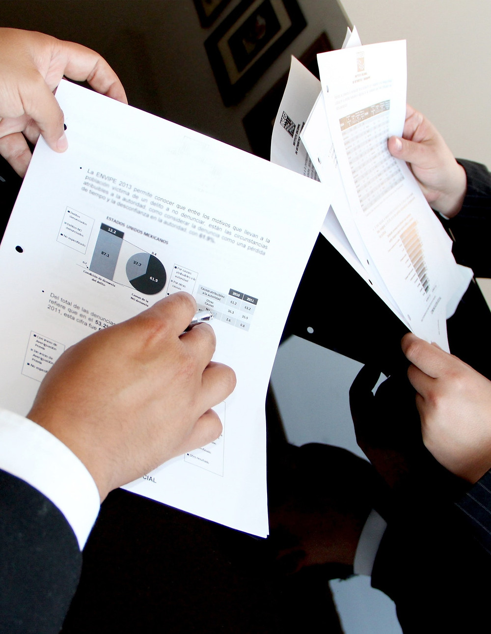 Two colleagues showing paperwork to each other
