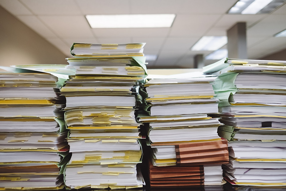 Photograph with lots of paperwork stacked on a table