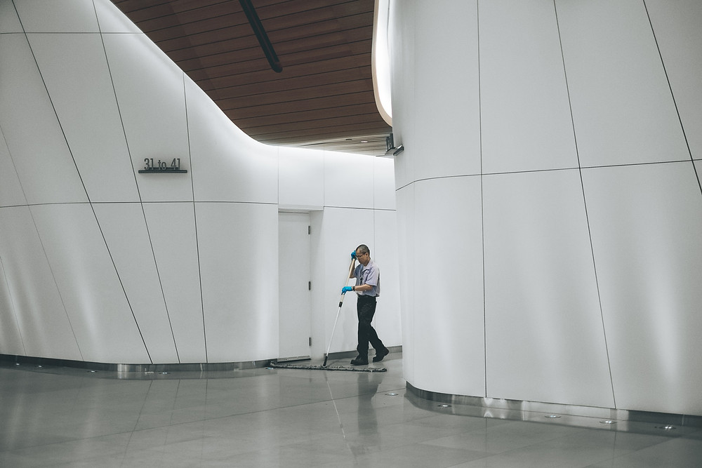 Photograph of an office building with a cleaner in the centre mopping the floors