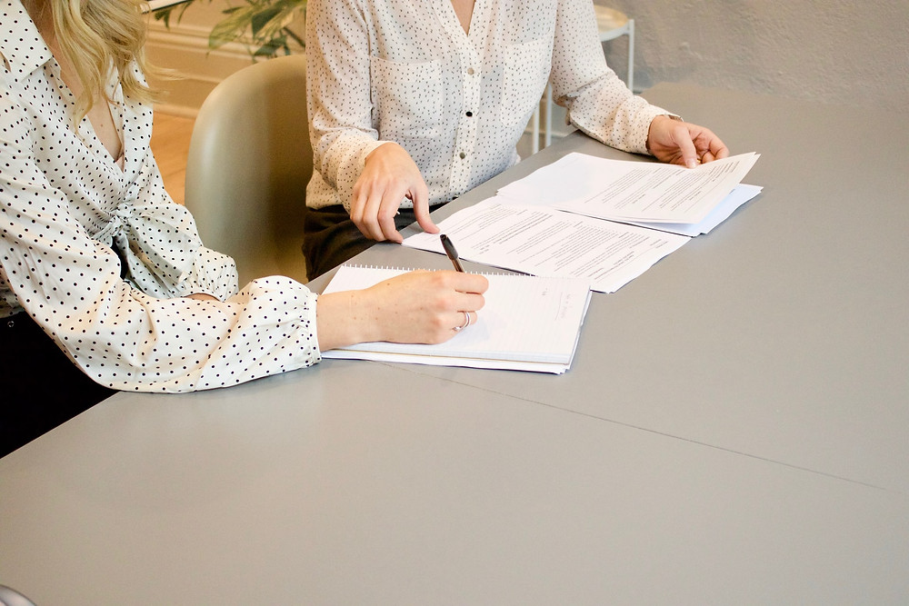 Two females sitting side by side signing papers at work