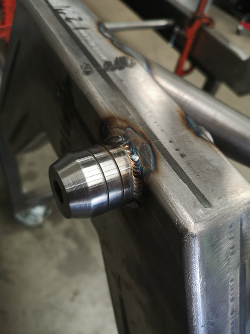 Through-chassis weld in suspension mounts
