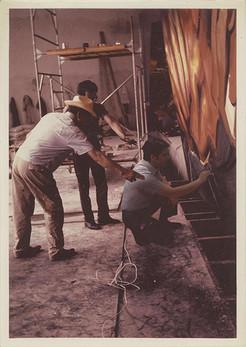 """David A. Siqueiros, Mario Orozco y Humberto Márquez durante el proceso de realización de uno de los tableros para el mural """"La Marcha de la Humanidad"""". Cuernavaca, Morelos. 1967"""