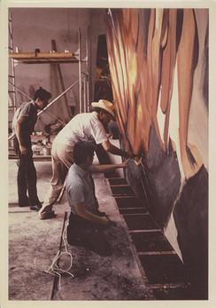 """Mario Orozco, David A. Siqueiros y Humberto Márquez durante el proceso de realización de uno de los tableros para el mural """"La Marcha de la Humanidad"""". Cuernavaca, Morelos. 1967"""
