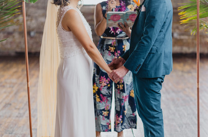 Closeup photo of the bride and groom holding hands while the wedding officiant from Once Upon A Vow speaks into the microphone in Greenpoint Loft
