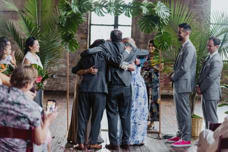 Photo of group hug family moment during the ceremony between parents and their children, the soon-to-be newlyweds after the ring warming led by modern officiant from Once Upon A Vow as guests and the wedding party looks on, framed by the tropical leaves ceremony backdrop in Brooklyn's Greenpoint Loft