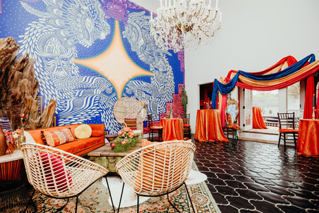 Photo of beautiful large living room area with large blue and yellow mural and colorful fabric installation with orange couch and velvet tablecloth over high cocktail tables