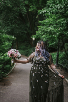 Portrait of purple-haired bride wearing an olive green sequined dress holding the bouquet in her right hand away from her as she stares at it, she is centered in a clear path surrounded by trees and greenery in Central Park