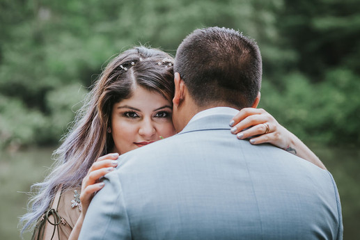 Photo of the couple hugging from the angle of the groom's back while the bride looks straight into the camera as she hugs the groom with the Central Park greenery in the background