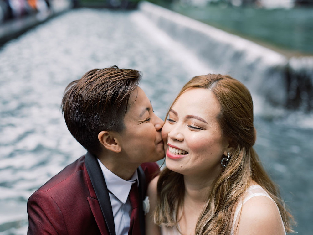 Butch/femme Asian couple; masculine presenting bride kissing the cheek of her femme presenting bride; both are smiling and have their eyes closed simply enjoying this moment post ceremony performed by queer officiant at Once Upon A Vow.