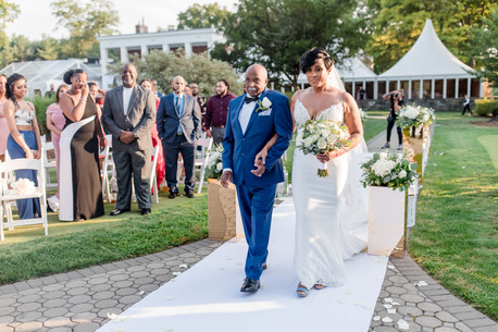 Beautiful bride walks down the aisle linking arms with father dressed in a royal blue suit while standing guests look on before the bilingual wedding ceremony officiated by Once Upon A Vow begins