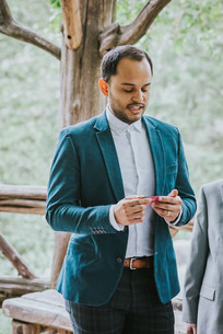 Photo of groomsman and bride's brother wearing a teal blazer looking down at a piece of paper, reading an excerpt of a quote during the Spanish elopement ceremony held in Cop Cot, Central Park