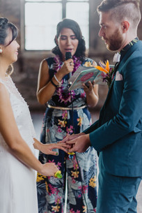 Close up photo of groom placing the ring on bride's left ring finger while officiant from Once Upon A Vow speaks into microphone and holds a colorful ceremony book in hand; bride's beaded overlay twinkles, set in Brooklyn's Greenpoint Loft