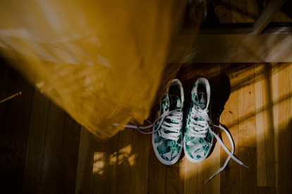 Flat lay view of tropical green-leaf converse sneakers with ombre yellow veil slightly out of focus hanging above pre-ceremony in Greenpoint loft apartment