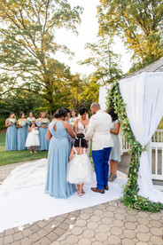 Wide angle of ring warming ceremony with family of five, the bride, groom, son, and two daughters being led by bilingual wedding officiant at Once Upon A Vow as bridesmaids look on towards the gazebo located at Pelham Bay Golf Course in the Bronx