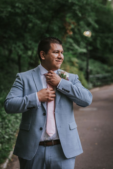 Portrait of the smiling groom fixing his pink tie while looking towards the right of the screen in Central Park