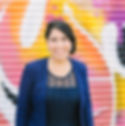 smiling, bilingual spanish and english speaking wedding officiant in blue dress and blazer with colorful mural background in Brooklyn, NY